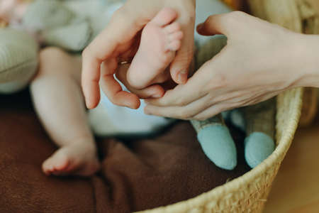 Baby feet in mother hands. Mom and her Child. Happy Family concept. Beautiful conceptual image of Maternity Banco de Imagens