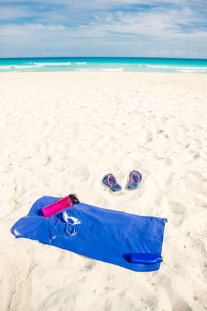 vacation and summer holidays concept - flip flops, towel, bottled water and bottle of sunscreen oil on beach sand.