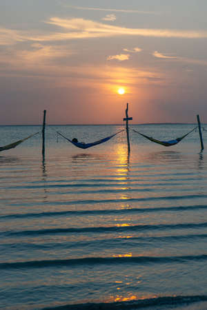 Relaxing in a hammock over the water, Isla Holbox, Mexico.