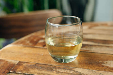 Glass of white wine on vintage wooden table Banco de Imagens