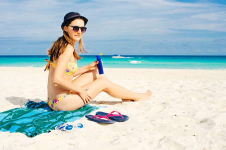 Woman applying sunscreen on her legs before sunbathing. Skin care with protection cream in summer time on the beach. Banco de Imagens
