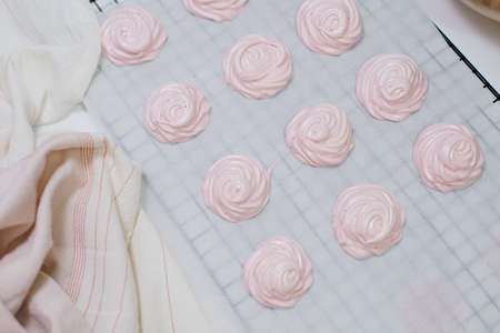 Homemade pink marshmallows on baking paper background on the kitchen