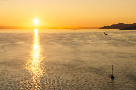 Golden Sunset into the sea with the silhouette of ship.