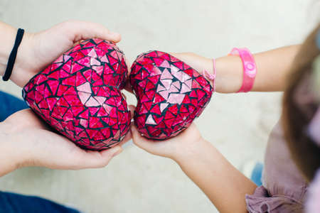 red hearts in the hands of a child and mom. view from above Stok Fotoğraf