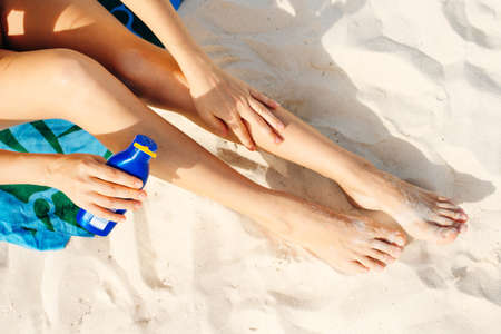 Woman applying sunscreen on her legs before sunbathing. Skin care with protection cream in summer time on the beach. Banco de Imagens - 151432111