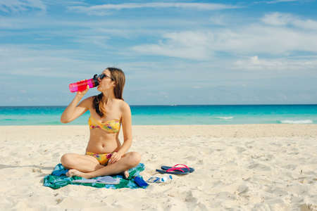 Young woman drinking sparkling water from transparent bottle on the beach, cancun Banco de Imagens