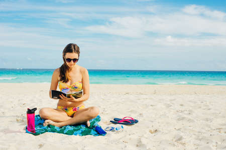 Summer Vacation. Smelling tourist women relaxing and reading book with sunglasses in beach Banco de Imagens