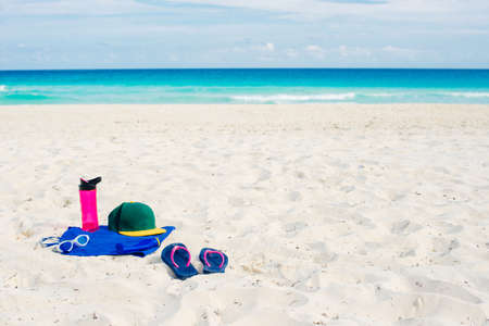 vacation and summer holidays concept - flip flops, towel, cap, bottled water and bottle of sunscreen oil on beach sand.