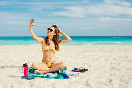 Young woman in a swimsuit in the sand makes selfie on the beach on her smartphone Banco de Imagens