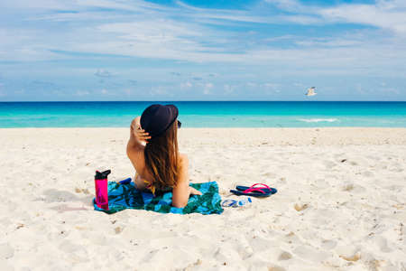 paradise summer vacation happiness carefree happy woman relaxing sitting in sand enjoying tropical beach destination. Banco de Imagens - 151608269