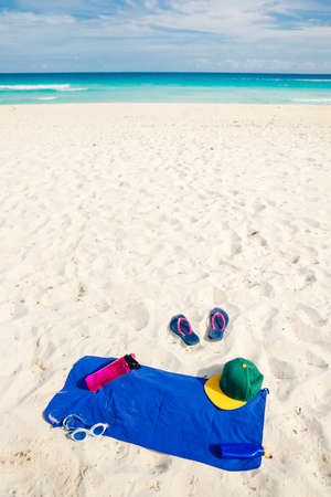vacation and summer holidays concept - flip flops, towel, cap, bottled water and bottle of sunscreen oil on beach sand Stok Fotoğraf