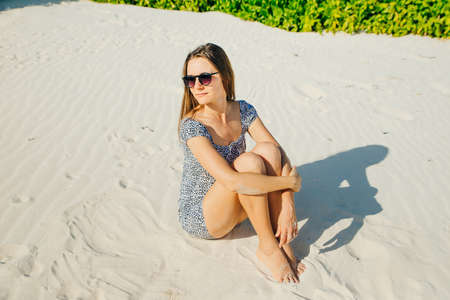 Sensual portrait of a young woman against a background of bushes. Romantic image. A woman lies on the sand.