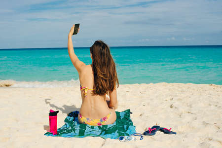 Young woman makes selfie on the beach on her smartphone.