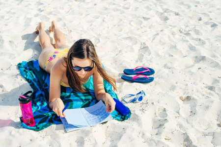Summer Vacation. Smelling tourist women relaxing and reading book with sunglasses in beach, mexico Foto de archivo