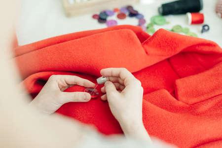a seamstress sews a button on a red coat. Zdjęcie Seryjne