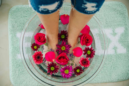 Foot bath in bowl with lime and tropical flowers, spa pedicure treatment, top view.
