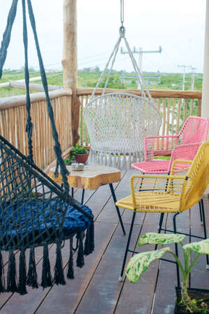 multi-colored wicker chairs on the balcony. 스톡 콘텐츠