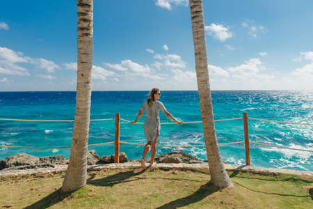 girl stands with her back against the blue ocean between palm trees. Cancun Mexico. Standard-Bild