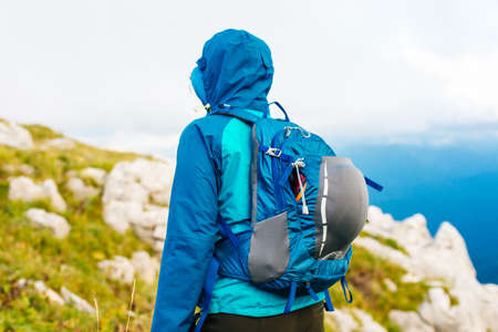 girl in a blue jacket with a hood and a city backpack in the Adygea mountains, Russia. Archivio Fotografico - 150761335