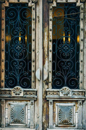 Wooden doors with carved decoration and glass.