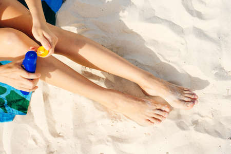 girl enjoys sunscreen on the sand. close view of the legs. Relaxing in holidays.