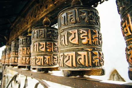 Prayer drum. Old prayer cylinders in Nepal. Tibetan Prayer wheels. Buddhist rolls in row