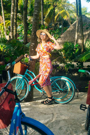 beautiful girl in a hat and a bright dress on a bicycle in the jungle