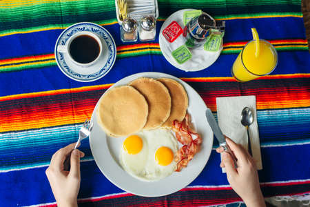 Tasty breakfast with pancakes, fried eggs and bacon on table.