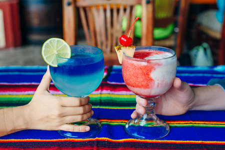 A man and a woman with multi-colored cocktails in their hands in restaurant Mexico