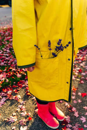 girl in a yellow raincoat holds lavender stalks in her hands. autumn