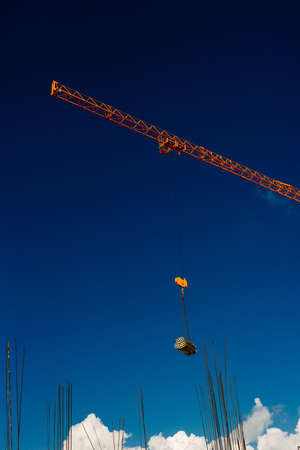 Yellow Industrial Cranes Working on Construction Site Against Blue Sky Banco de Imagens