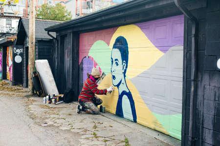 canada, toronto - december, 2019 Graffiti artist spraying the wall Editorial