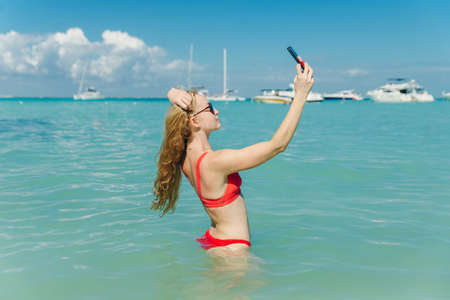 beautiful blonde in a red bathing suit makes selfie on the background on the beach Playa Norte, Isla mujeres. Mexico.