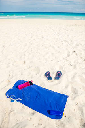 vacation and summer holidays concept - flip flops, towel, bottled water and bottle of sunscreen oil on beach sand. Imagens