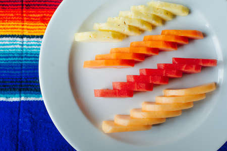 slices of fruit beautifully sliced on a white plate in a restaurant. Mexican food.