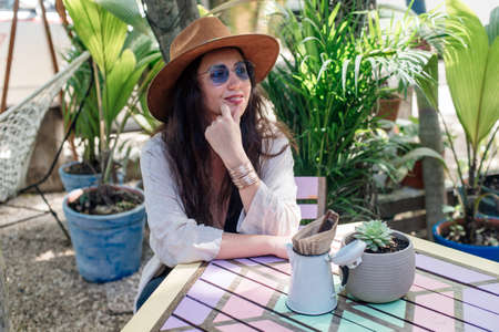 Attractive girl tourist in sunglasses, a blouse and a hat in a street cafe. The concept of tourism, travel, leisure Banco de Imagens