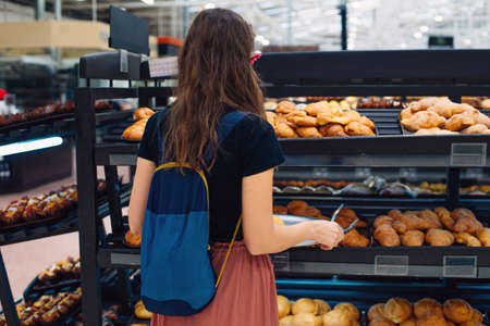 women choosing bread at the supermarket. bun tongs and tray. Banco de Imagens