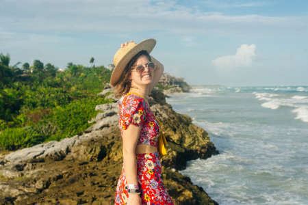 beautiful girl in a hat and a black dress looks at the ocean. TULUM, Mexico.