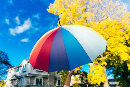 young woman standing with a multi-colored umbrella and rotates it against with a blue sky.