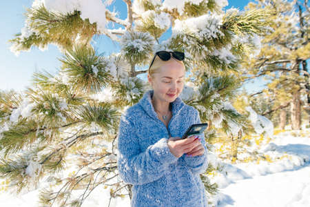 blonde girl writes sms in the winter forest.