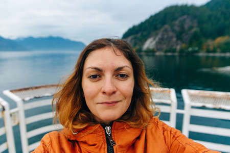 Traveler makes selfie on the background of the lake. Vancouver, Canada