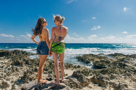 Cancun, Quintana Roo, Mexico. beautiful girls stand on a background of blue ocean