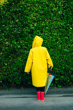 girl in a yellow raincoat on a background of a wall with grass Reklamní fotografie