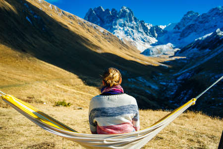 The girl lies on a hammock in the background of the mountains. Caucasus Mountains in Georgia