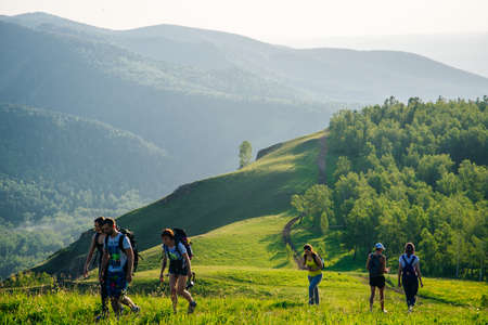 Russia, Krasnoyarsk - june, 2019 tourists go hiking through the green hills Editorial