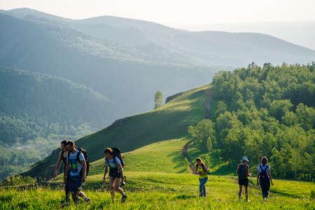 Russia, Krasnoyarsk - june, 2019 tourists go hiking through the green hills Redakční