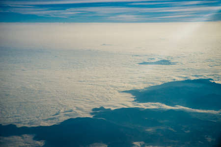Plane window view of clouds and islands surrounded by sea and airplane wing. Traveling concept