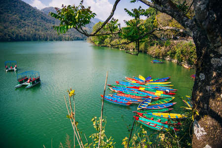Phewa Lake with multicoloured boats in the valley of Pokhara in central Nepal. Banco de Imagens