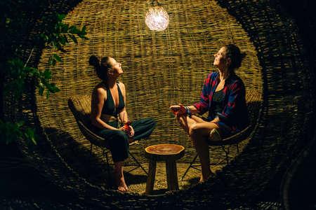 girls drink wine in Rattan lounge at night, mexico, tulum Stok Fotoğraf