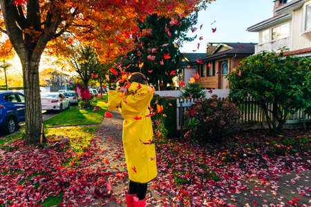 Beautiful girl in the yellow raincoat walking outdoors in autumn. Young woman enjoying autumn weather.
